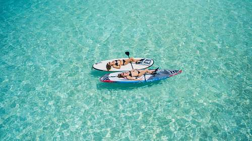 maldives two woman on surfboard floating on water water