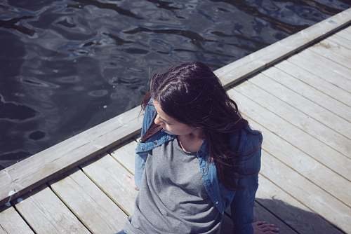 person woman in grey top seating on dock during daytime human