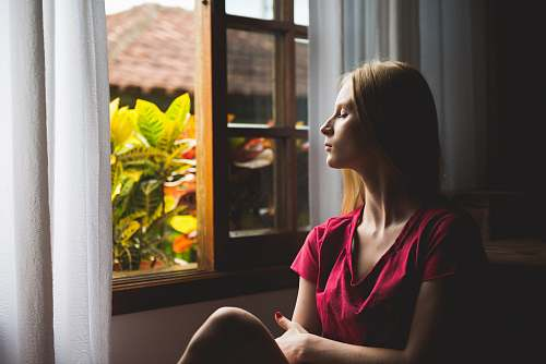 human woman sitting near open window plant