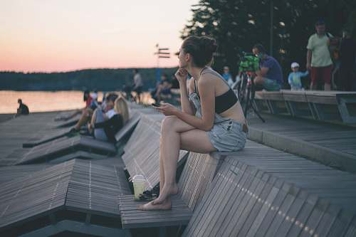 photo person woman sitting on top of wooden bench near people and beach human free for commercial use images