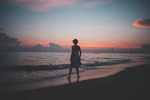 person woman standing on the seashore during golden hour human