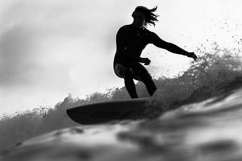 black-and-white grayscale photo of man riding a surfboard people