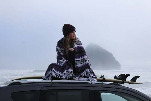 human woman wearing beanie hat on vehicle roof people