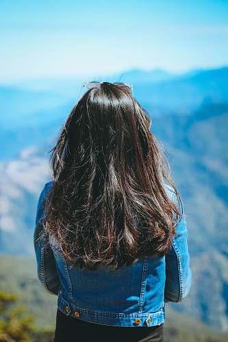 woman woman wearing blue denim jacket standing near mountain people