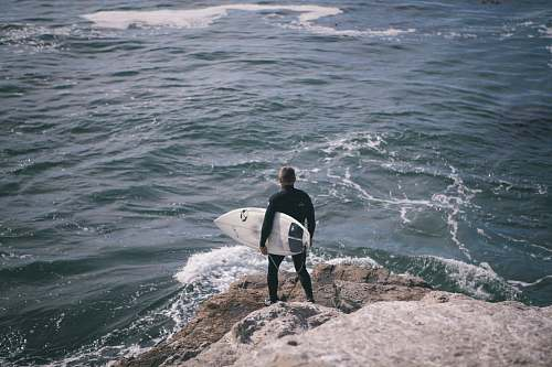 photo ocean man holding surfboard standing in front of sea person free for commercial use images