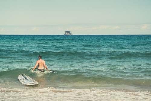 ocean man in water beside surfboard beach