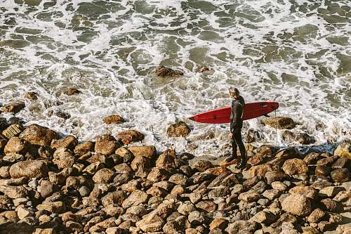 photo water person holding surfboard near seashore during daytime ocean free for commercial use images