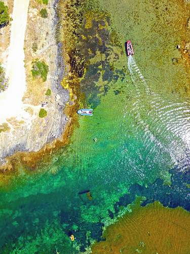 bay aerial photography of red and blue boats aerial view
