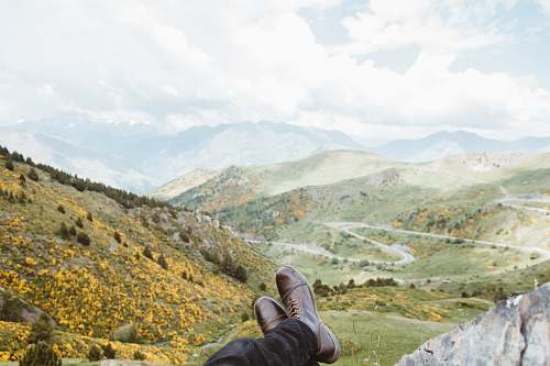 clothing person wearing brown leather boots near mountains at daytime shoe