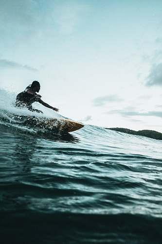 surfing man surfboarding during daytime ocean