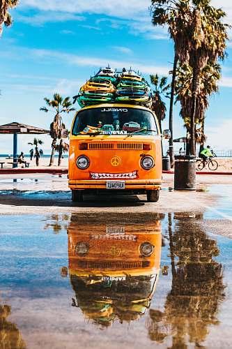 car orange van with surfboard on top beach