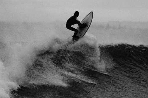 photo ocean grayscale photo of a man surfing black-and-white free for commercial use images