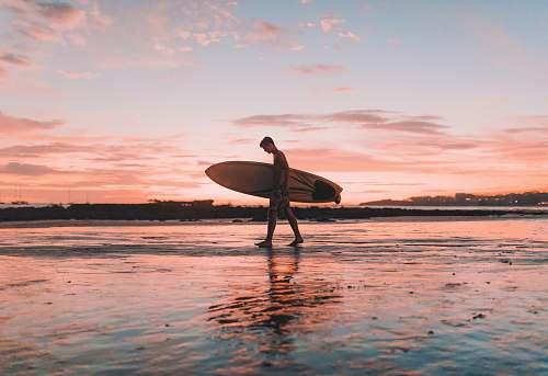 water man holding surfboard walking near seashore surfboard