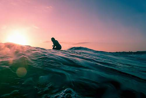 water man surfing on ocean water during golden hour nature