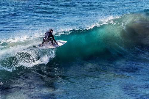 photo ocean person on white surfboard surrounded by blue ocean water during daytime sea free for commercial use images