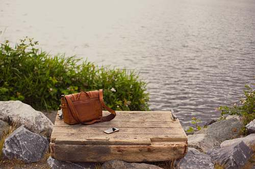 photo bag brown leather crossbody bag on brown wooden panel near water seattle free for commercial use images