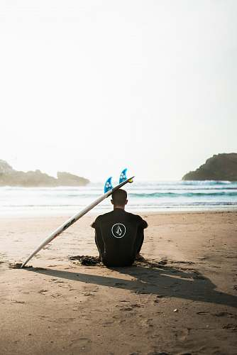 photo ocean man sitting on sand beside surfboard facing sea during daytime sea free for commercial use images