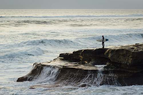 sea person carrying surfboard standing near seashore coast