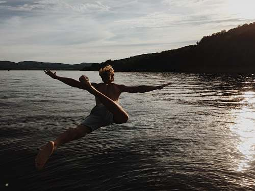 stretch person jumping to body of water lake