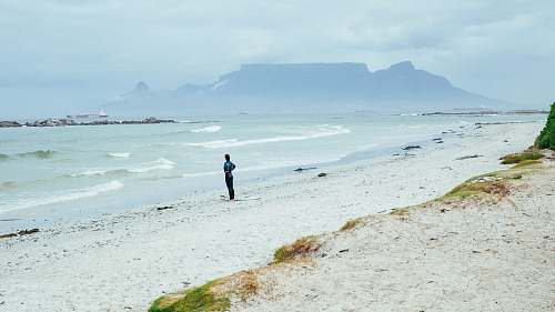 photo ocean person standing on shore near mountain covering of fogs at daytime sea free for commercial use images