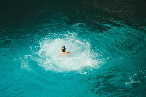 jamaica photo of person swimming on body of water blue