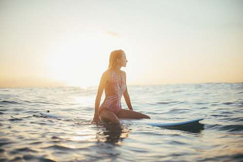 bikini woman riding a blue surfboard in a body of water clothing