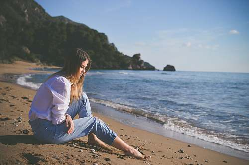 photo beach woman sitting on beach shore during daytime woman free for commercial use images