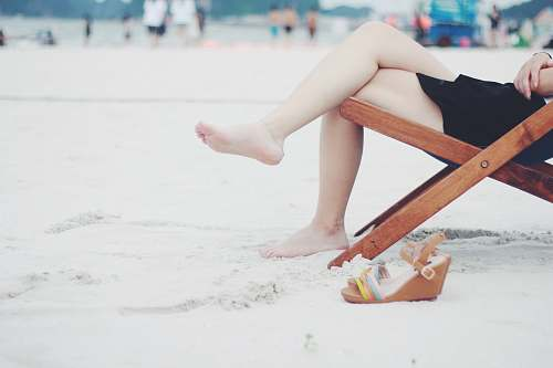 people person seats on brown folding chair during daytime beach