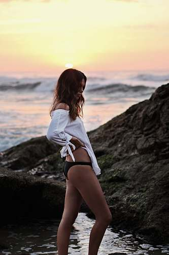 photo people woman wearing white off-shoulder shirt and black panty standing on shore with large rock during golden hour girl free for commercial use images