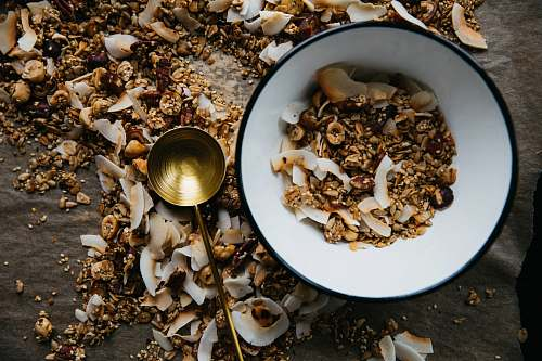 granola bowl beside brass-colored ladle seafood