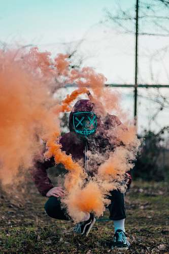 clothing person in purple hoodie releasing orange smoke smoke