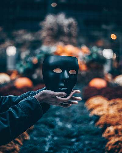 person person holding black mask mask