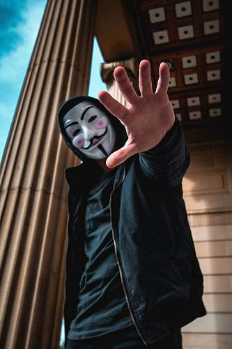 human man wearing Guy Fawkes Mask standing inside building person