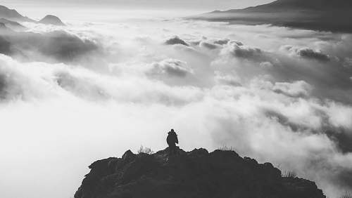 grey person standing at the edge of a mountain facing clouds during day mountain