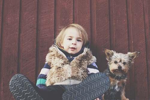 kid boy sitting on floor brside dog animal