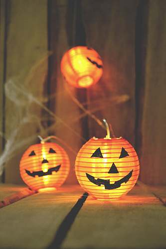 photo pumpkin three jack-o-lantern lamps on beige wooden board autumn free for commercial use images