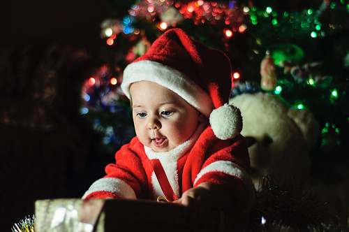 people baby wearing Santa Claus outfit near Christmas tree person