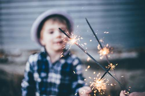 person closeup photo of boy wearing blue and white plaid sport shirt holding firework kid