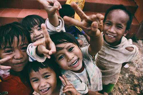 people five children smiling while doing peace hand sign kid