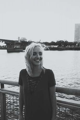 person grayscale photo of smiling woman standing near fence above body of water grey