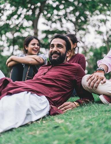photo people man in maroon dress shirt lying on green grass field smile free for commercial use images