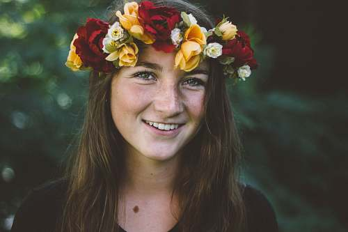 person selective focus photography of smiling woman wearing floral headdress flower