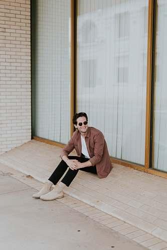 person smiling man sitting in door front flooring