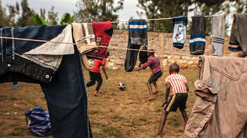 photo person two boys playing under clothesline kenya free for commercial use images