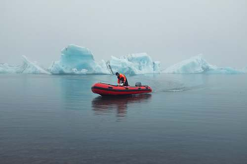 nature man riding inflatable boat near icebergs outdoors