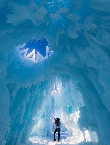 glacier woman taking photograph in ice cave snow