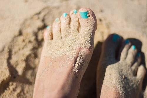 foot person sky-blue nail polish feet on brown sand beach