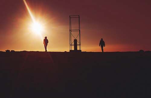 sunrise silhouette of two person near gray metal frame during sunet sunset
