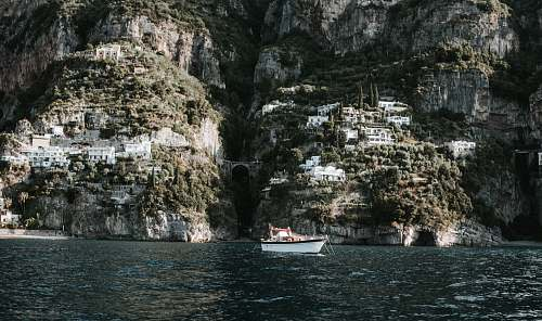 cliff white motorboat on body of water boat