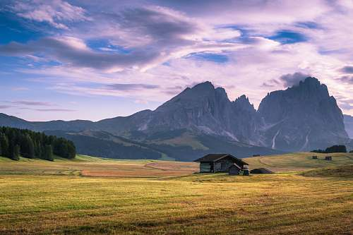 italy gray wooden house on green plains near mountain range at daytime outdoors